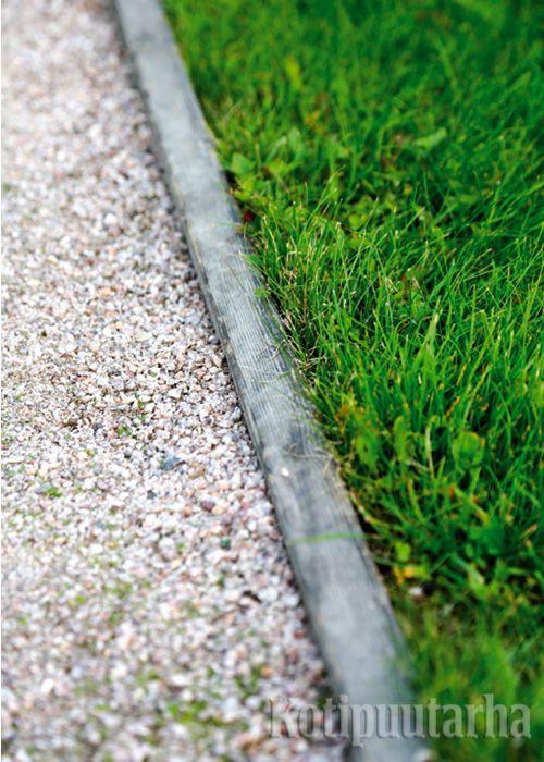 Maahan upotettu lauta rajaa nurmikon hiekkakäytävästä.