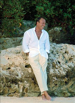 Julio Iglesias wearing the Miami uniform for men: white shirt, tan pants, shoes optional.