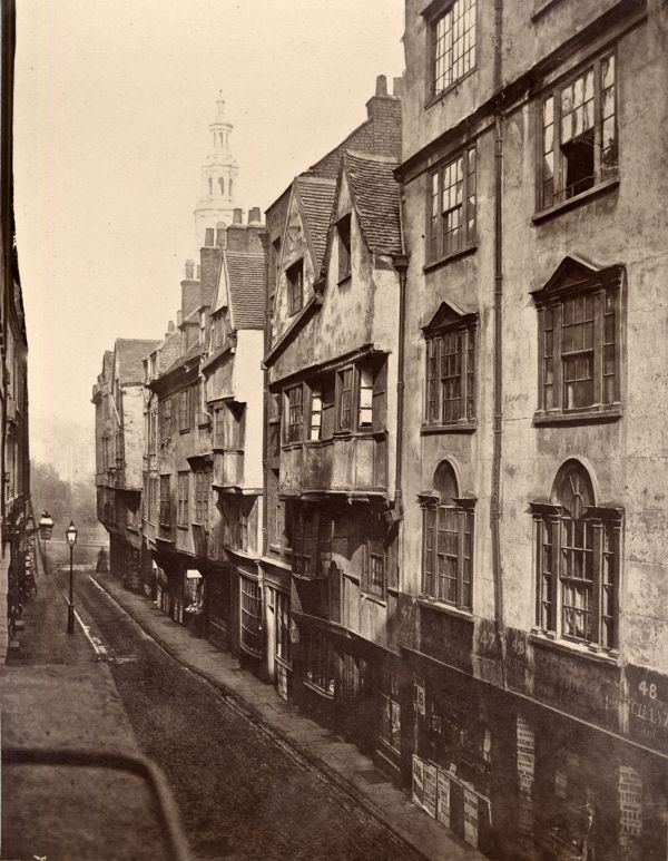 A woman turns the corner into Wych St. http://spitalfieldslife.com/2010/12/26/the-ghosts-of-old-london/