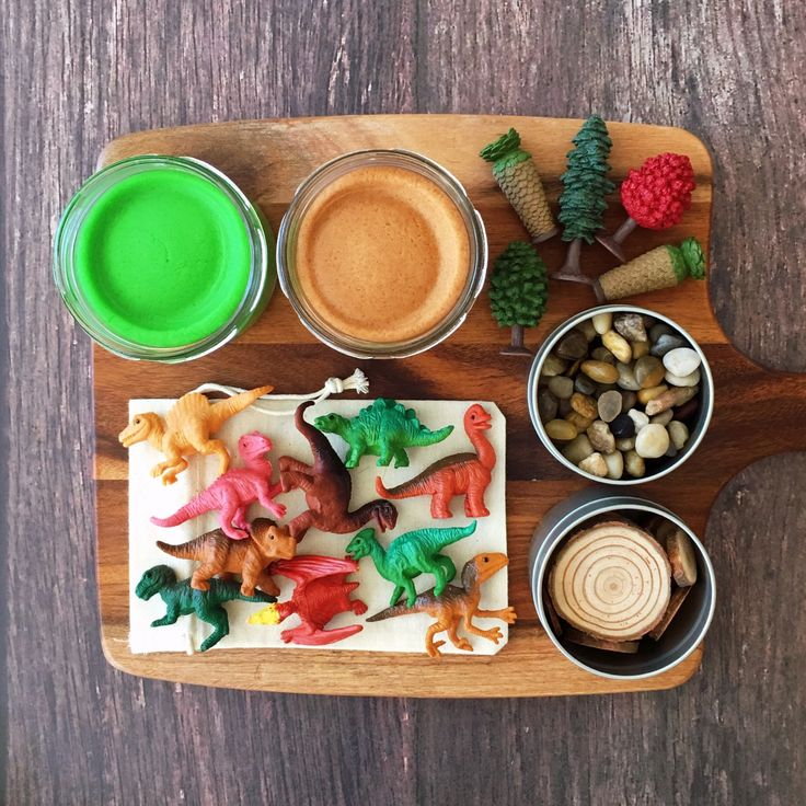 Dinosaurs sensory play kit with playdough, stones, wood slices and little trees.