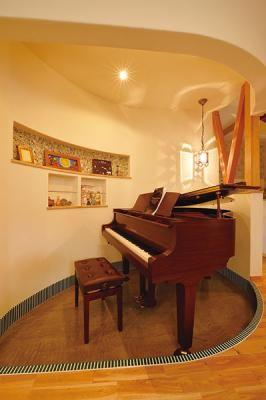アールを生かした木の葉型のスペースにグランドピアノを配置。こちらは一段低くして周りをタイルで演出。ニッチにもタイルを使っておしゃれに。