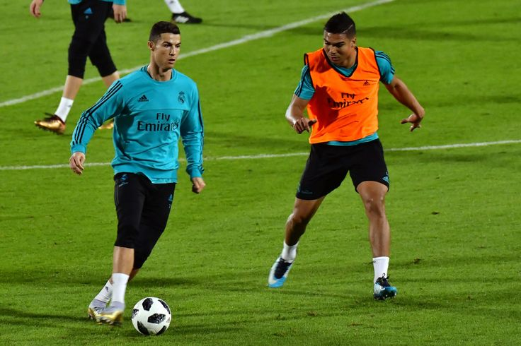 Cristiano Ronaldo Photos - Real Madrid's Brasilian midfielder Casemiro (R) vies for the ball against his Portuguese teammate forward Cristiano Ronaldo during a training session two days prior to his team's FIFA Club World Cup semi-final match at New York University Abu Dhabi's stadium in the Emirati capital on December 11, 2017. / AFP PHOTO / GIUSEPPE CACACE - Real Madrid Training in Abu Dhabi Before Their FIFA Club World Cup Semi-Final