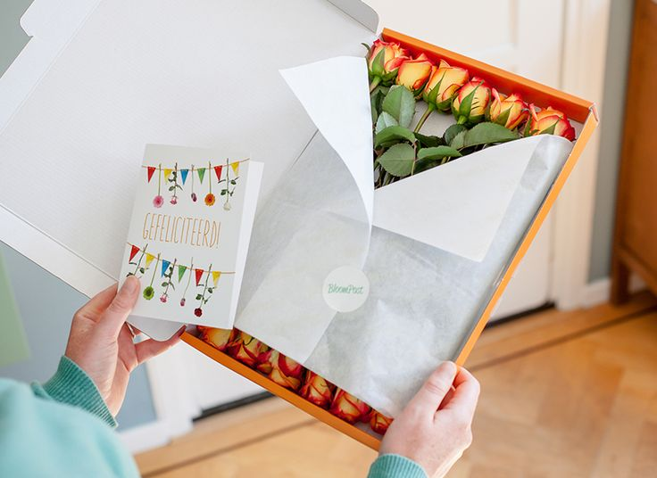 Bos vlammend oranje rozen door de brievenbus met een persoonlijk kaartje
