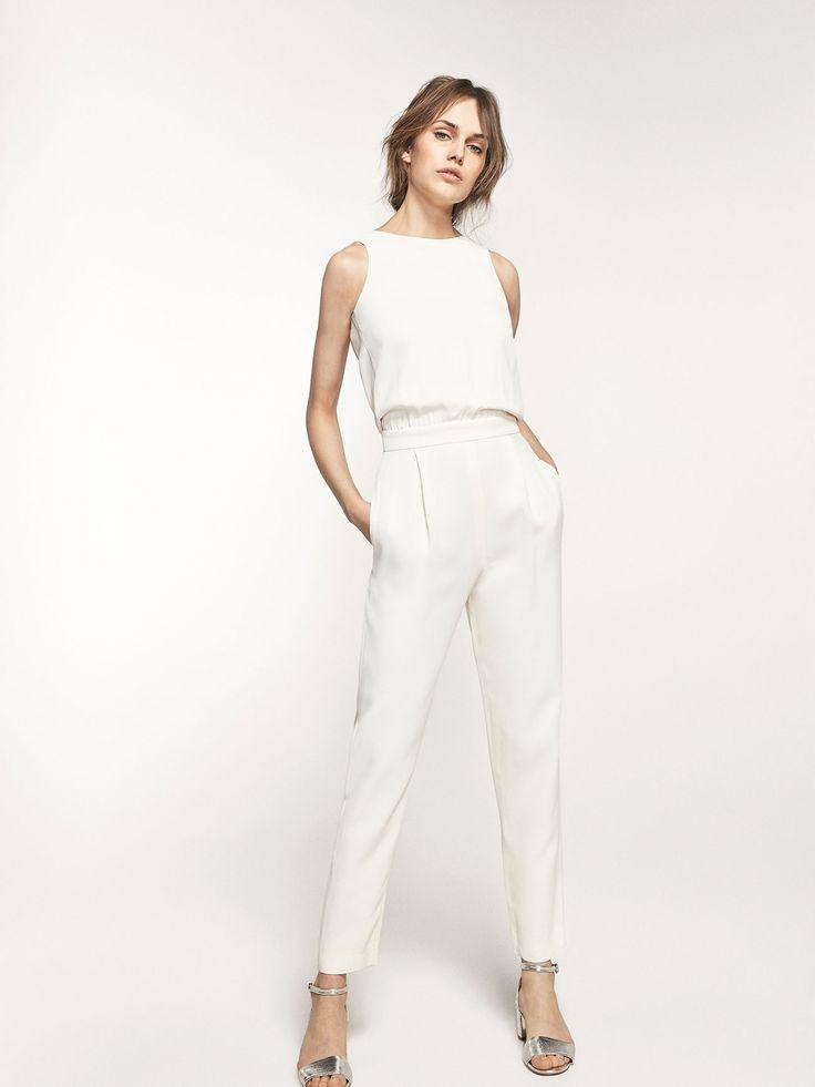 Combinaison blanche ornée d'un nœud décoratif dans le dos. Modèle sans manches de coupe slim, col rond, fermeture éclair dans le dos, deux poches sur les côtés, pinces sur le devant, doublure.