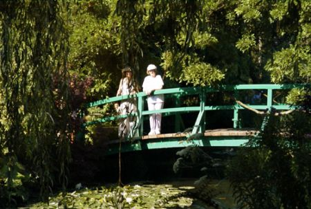 "The Ghost On The Bridge ""My wife and I visited Monet's garden at Giverny in 2002 and as true tourists took photographs of each other on the bridge over the lily pond. After waiting for the bridge to be more or less clear of other people I took 2 photos of my wife, one with a conventional film camera  the other with a digital camera ( these within moments of each other).On processing the pictures we were amazed to see a figure of a woman,apparently standing next to my wife, on the digital…"