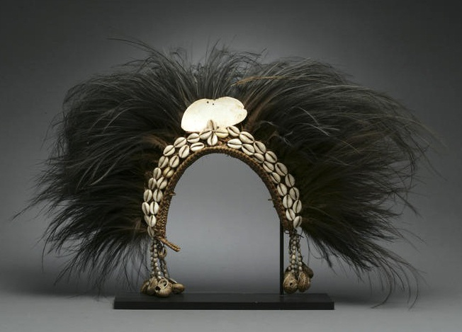 Papua New Guinea | New Guinea headdress of classical form, with cowrie shell headband, a large ovoid shell apex, and strings of seeds and shells to either side; the whole crowned with a dense spread of black cassowary feathers | Est. 2,500 - 3,500$