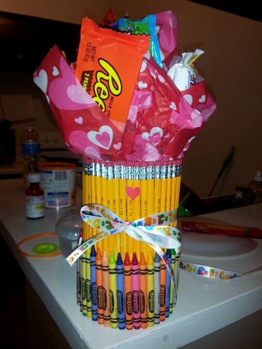 teachers valentines present! First a spray glued a similac baby formula can.. Then I put all the pencils on and then put a rubber band so they could stick.. Next day I sprayed bottom of pencils and put crayons on.. Same thing put rubber band so it could stick... Then I poked lid to can with the sticks and taped candy to sticks and then added tissue paper.. The teacher loved it :)