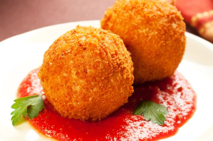 Sausage-filled risotto balls served in a pool of Francesco Rinaldi Original Recipe Pasta Sauce. Try this recipe tonight!