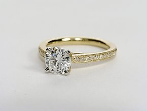 Elegant with a touch of vintage, this diamond engagement ring setting features pavé-set diamonds in a delicate 18k yellow gold milgrain design to frame your center diamond. 1/8 carat total diamond weight. #bluenile
