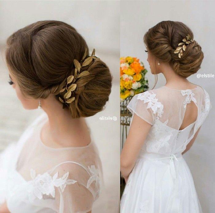 Acconciatura da sposa in un basso chignon racchiuso da accessori color bronzo