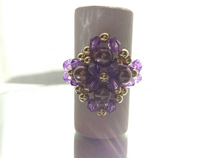 Anillo tejido en tonos violetas y dorado.