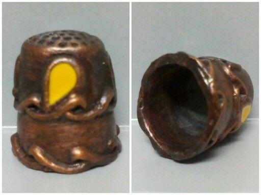 DEDAL DECORADO CON ESMALTE, este dedal esta inspirado en motivos utilizados en la época medieval, destacando las ondas de la base como característica principal y los detalles de esmalte de colores del cuerpo central