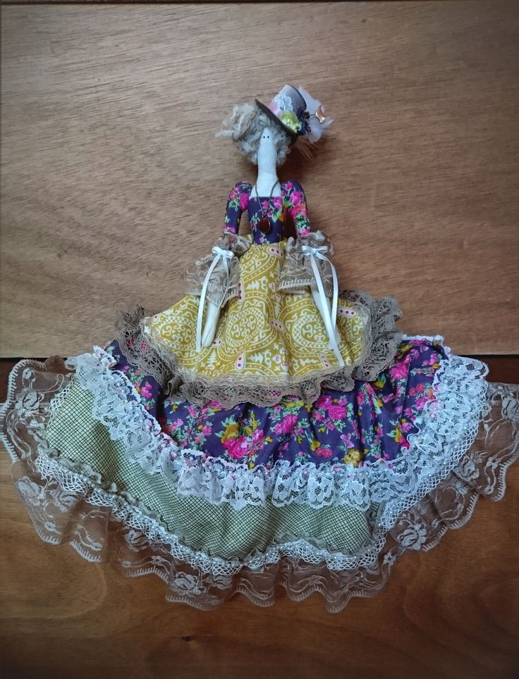 - Tilda Doll - Dressed in a long skirt decorated with lace and pearls. The doll is also embellished with a golden necklace and a top hat with feathers.
