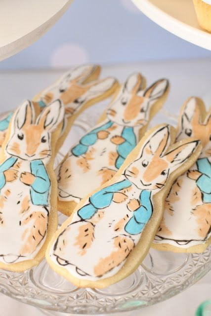 Peter Rabbit for a little boy named Peter! Beautiful pastels used throughout the birthday party, from the invitations to the drinks in charming little milk bottles, tablescape of sweets and cake hung with charming bunting. Hello Naomi - cake, cookies, cupcakes and styling Imprintables - wallpaper, invitation, banner, cake stands