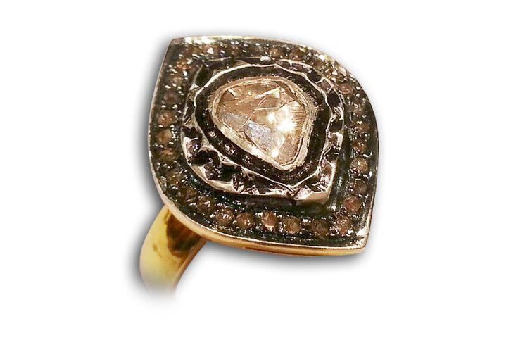 18 KARAT YELLOW AND WHITE GOLD RING WITH BLACK DIAMONDS AND INDIAN POLKI DIAMOND CENTRE.