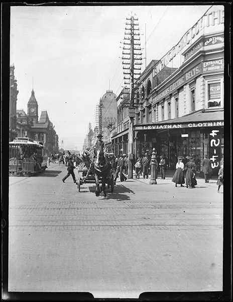 It was a brave photographer who stood in the middle of the street in the path of an oncoming carriage to capture this shot of a Melbourne street c. 1900. To the left of the carriage is the Carlton tram. Looks like cnr Swanston and Bourke Streets)  Photography by unattributed studio.