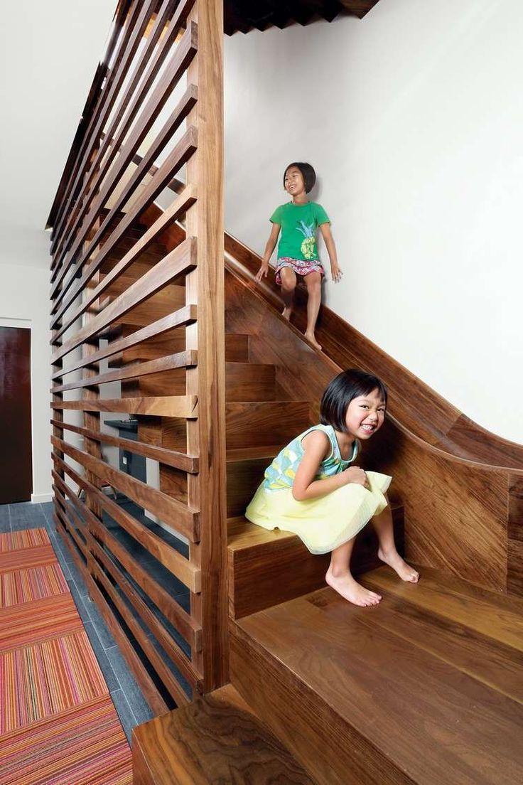 maison avec toboggan en bois massif installé parallèlement à l'escalier droit, carrelage sol gris anthracite et tapis multicolore