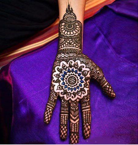Intense mendhi with blue glitter used to highlight the central flower motif