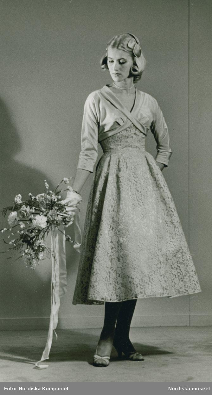 Brud och Hem, 1957. Modell i siden- och spetsklänning, pärlhalsband, blombukett och handske. Foto: Erik Holmén för Nordiska Kompaniet