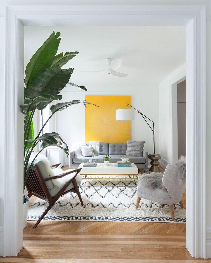 Soggiorno scandinavo minimal con un quadro giallo sole di grandi dimensioni. Bella idea per portare l'allegria nella stanza