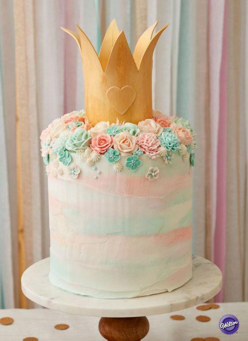 Learn how to make this stunning birthday cake that's straight out of a fairy tale! Topped with a gold crown and a field of pastel flowers, this Fairy Princess Birthday Cake cake will add a very happily ever after to any birthday celebration.