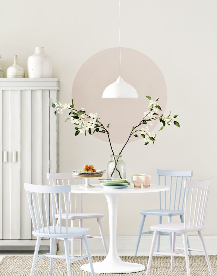 Upgrade a neutral dining room with pastel shades and sophisticated walls.  Here, a plain vanilla wall has been given an impact with a large simple circle of nude paint.  Not only does it make a stylish statement it also highlights a delicate pendant light hanging above the modern circular dining table