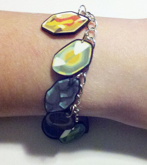 This charm bracelet contains charms of all of the stones used to evolve pokemon in the main series of games. On 7.5 silver chain with a bar toggle clasp, you have the following (in no particular order): Everstone Leaf Stone Fire Stone Thunderstone Water Stone Shiny Stone Sun Stone