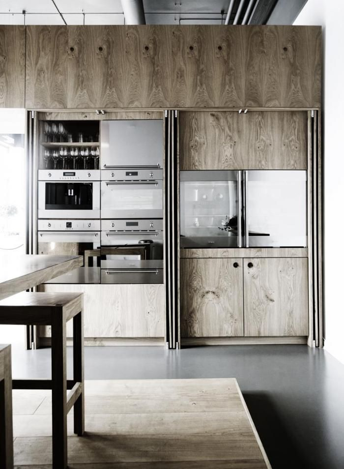 All appliances are concealed behind full-length oak cabinet doors in this kitchen by Danish company Kobenhavns Mobelsnedkeri.