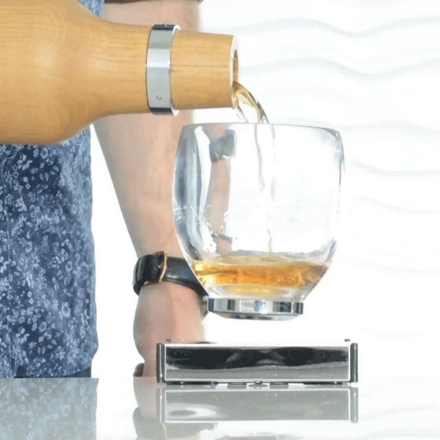 """Levitating Cocktail Glass. Using quantum locking (no joke) the glass is """"locked"""" mid-air above the plugged in base unit. From Oak Bottle, via Fancy; $190."""