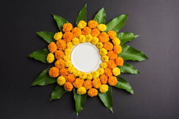 flower rangoli made using marigold or zendu flowers and mango leaves
