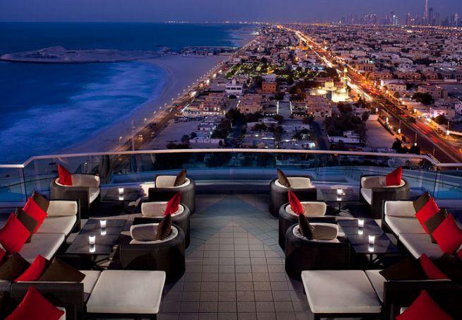 6 - Para brindar com os olhos: dez bares com cenários incríveis ao redor do mundo: UPTOWN BAR, EM DUBAI (EMIRADOS ÁRABES): DO 24º ANDAR DO JUMEIRAH BEACH HOTEL É POSSÍVEL VISUALIZAR O MAR, A MARINA E LUZES DOS ARRANHA-CÉUS GIGANTES DA NOVA DUBAI. O DESIGN CONTEMPORÂNEO E O MENU RECHEADO DE INGREDIENTES SOFISTICADOS COMPLETAM A PERFEIÇÃO DO LUGAR. Foto: Divulgação.