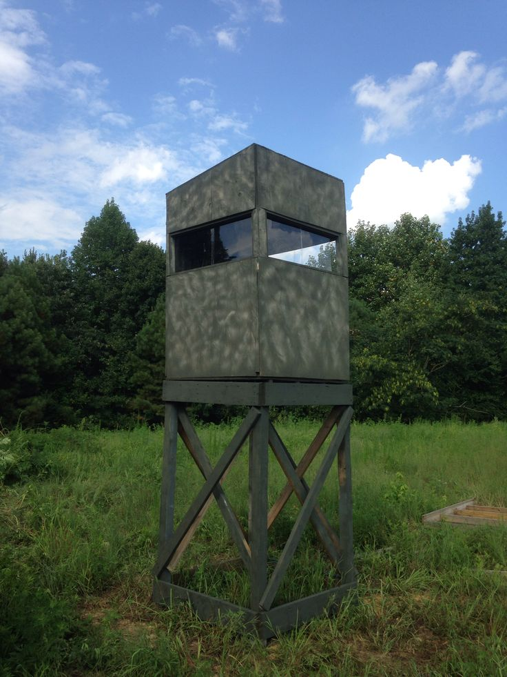 4x4 shooting house with sliding plexiglass windows camouflaged with camo spray paint and pine tree branch.