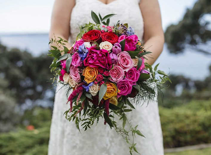 Bright bouquet of pink peonies, roses in orange red and pink, with blue belladonna, amaranthus and foliages. By www.blossomweddingflowers.co.nz