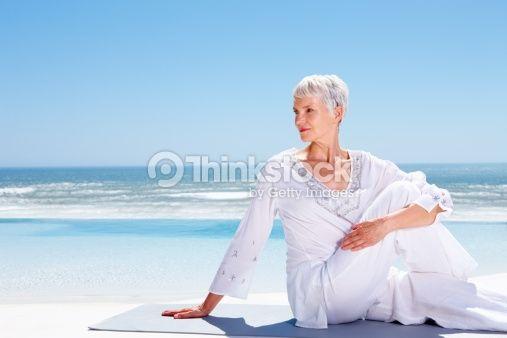 Stock Photo : Active senior woman exercising at beach