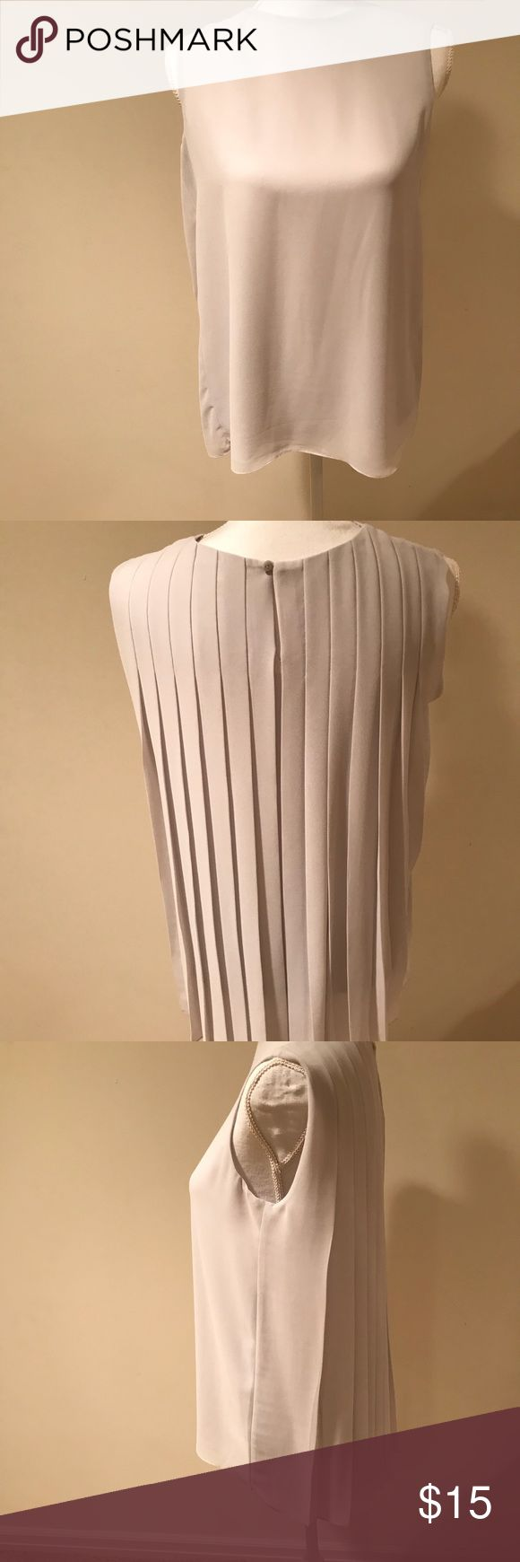 A Uniqlo blouse that is gently used. This Uniqlo blouse was worn twice. It is in excellent condition. This blouse is light grey and very lightweight. It is completely pleated in the back with a button closure at the base of the neck. Uniqlo Tops