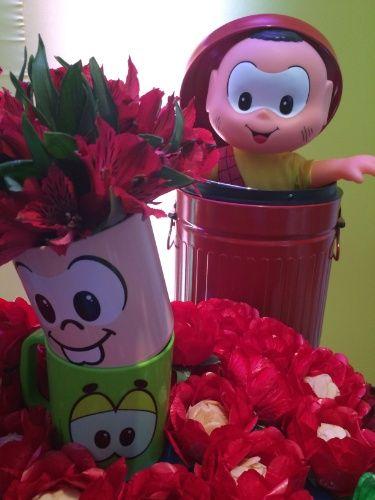 Canecas com o rosto dos personagens da Turma da Mônica serviram como vasos para os arranjos de alstroemérias vermelhas. Brigadeiros goumert de amêndoas, da chef Aline Leone, foram colocados em forminhas vermelhas