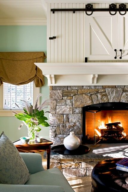rustic stone hearth contains a roaring fire, while sliding wooden barn-style doors above the mantel conceal a television.