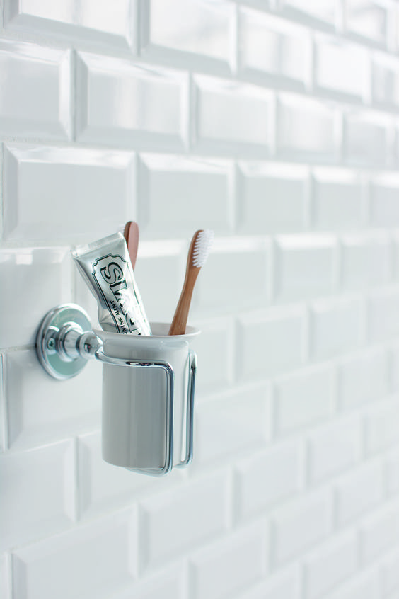 Luxury tumbler holder with Marvis toothpast and wooden toothbrushes. Minimal white bathroom with metro tiles.