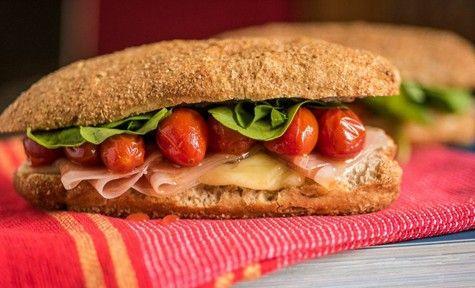 sanduíche de presunto cru com queijo estepe, tomates cereja assados e rúcula