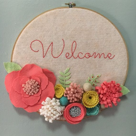 Embroidery Hoop Art, Wall Art, Door Sign, Welcome, 3-D felt flowers, coral, green, yellow, pink, blue and grey This hoop art is made with oatmeal (slight peach color) colored felt, handmade flowers and Welcome hand-embroidered. The background is stretched onto a 12-inch wooden embroidery hoop . The metal clasp on top is the perfect place to hang your hoop from a nail or pushpin. You could also prop it on a bookshelf or hang from a string or ribbon . CUSTOMIZE IT! Would you like to change…