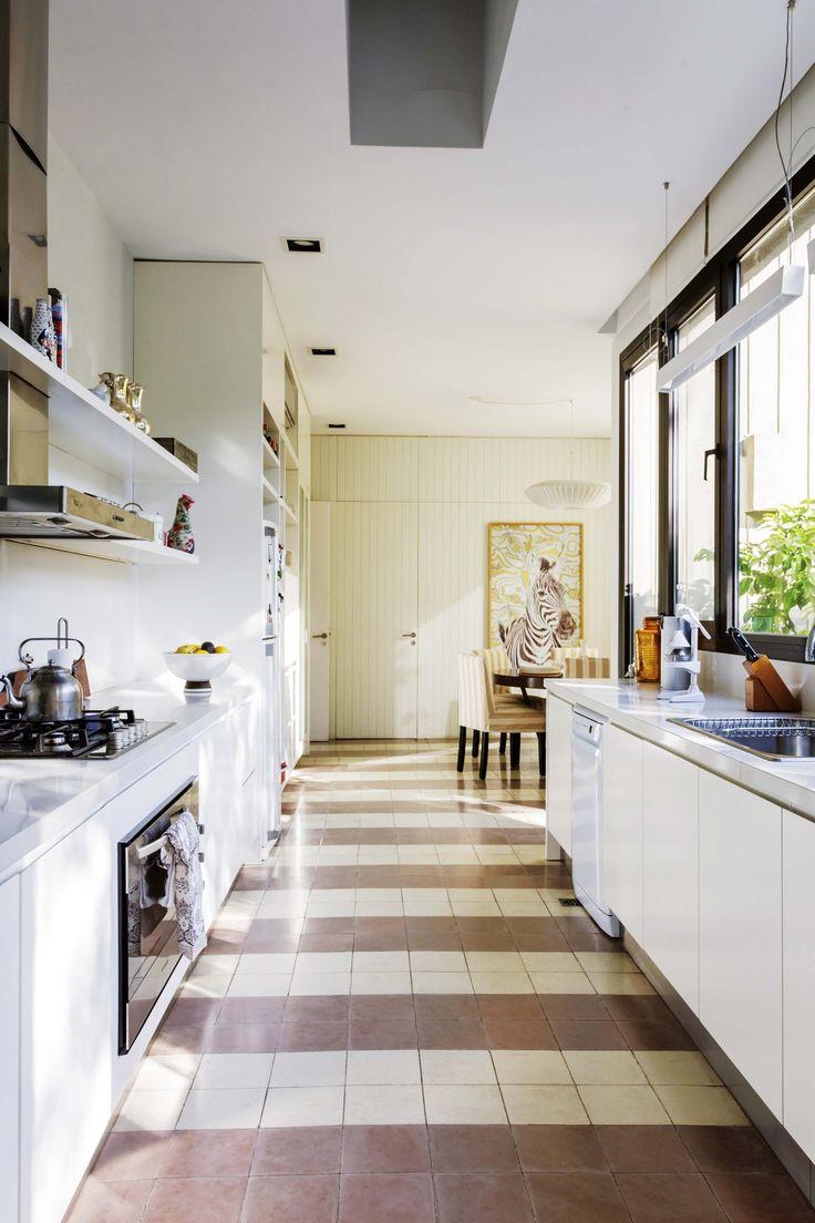 Cocina comedor de la casa de María Freytes con piso de calcáreos en dos tonos, colocado en una trama a rayas. Además, muebles bajo mesada y alacenas en blanco laqueado.