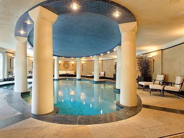 Large luxury indoor pool in Roman bath design with columns surrounding the oval pool.