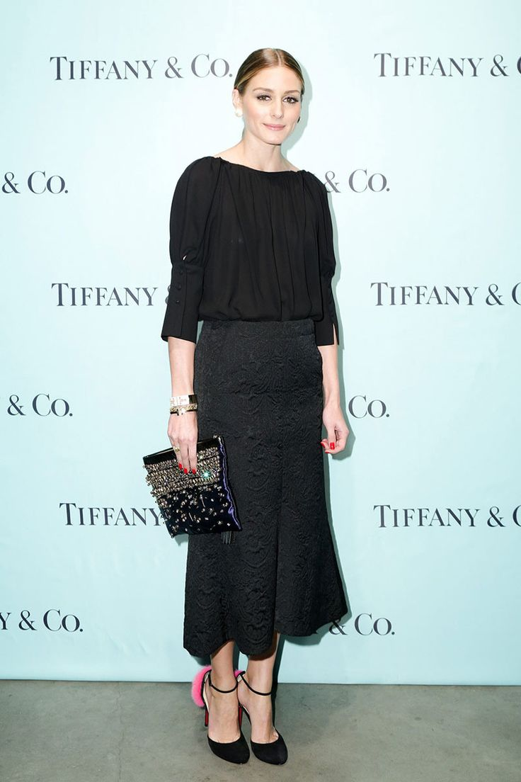 Olivia Palermo estuvo en la fiesta de apertura de la exposición The Tiffany T Train en Nueva York con una falda negra midi con brocados, una blusa negra, unas sandalias negras con un pompón rosa de Christian Louboutin y un clutch morado con pedrería.