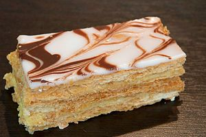 Traditionally, a mille-feuille is made up of three layers of puff pastry (pâte feuilletée), alternating with two layers of pastry cream (crème pâtissière), but sometimes whipped cream, or jam are substituted. The top pastry layer is dusted with confectioner's sugar, and sometimes cocoa, or pulverized nuts (e.g.  roasted almonds). Alternatively the top is glazed with icing or fondant in alternating white (icing) and brown (chocolate) stripes, and combed.