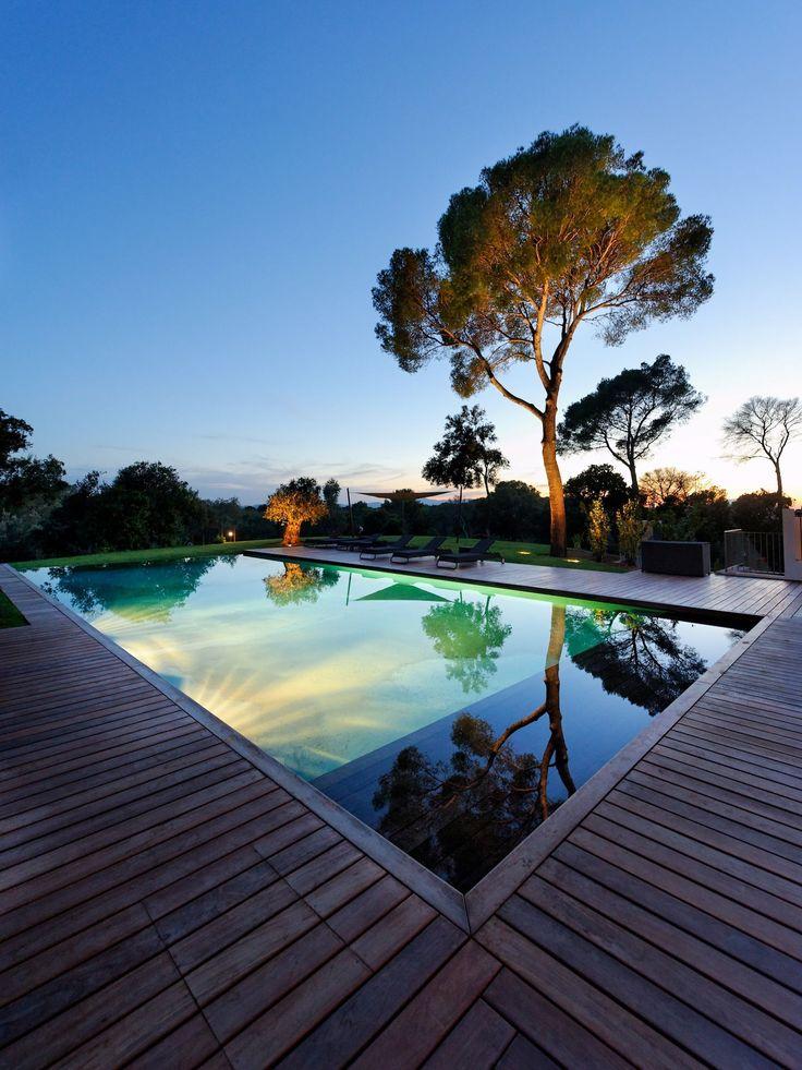 L'esprit nature par l'esprit piscine . 18 x 8 m . Revêtement gris clair . Escalier droit sur la largeur . Plage en ipé . Trophée d'Argent FPP 2012 de la piscine de nuit