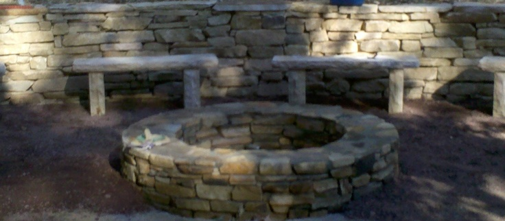 Greetings from Earth: A Place to Hang : Brown stack stone wall with firepit, stone benches, and crushed ore patio.
