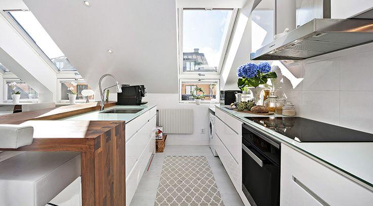 Stilrent kök från Ballingslöv med köksluckor i vitt, platsbyggda av fackman och kakelvägg ovanför diskbänken från Laura Ashley. Köket har en praktisk köksö med stor arbetsyta. Gott om förvaring i en moden tappning tillsammans med integrerade vitvaror.