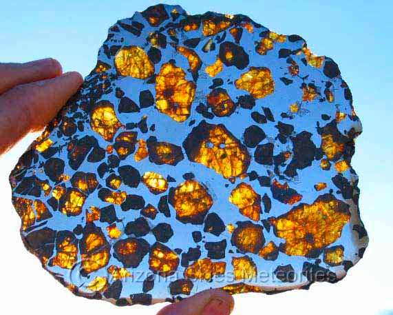 """Pallasite Meteorite: Pallasites are stony-iron meteorites derived from an extinct planet that was detroyed during the formation of our solar system approximately 4.5 billion years ago. They come from the boundary between the silica rich mantle and the iron-nickel core of the planet. Pallasites contain olivine (Peridot) """"space gems"""" embedded in an iron nickel matrix. When sliced thinly and polished, the stable pallasites make exceptional display pieces."""