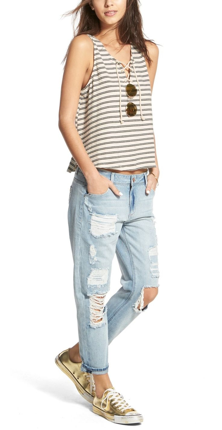 On trend: pairing distressed boyfriend jeans with a cropped tee and sneakers.