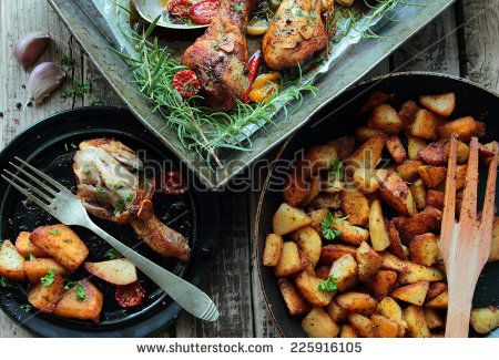 Roasted chicken legs with fried potatoes chips with herbs - stock photo